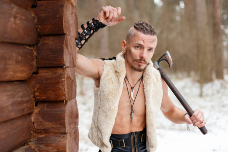 Viking with a scar with an ax in a woolen waistcoat near a wooden wall in the forest on a winter day