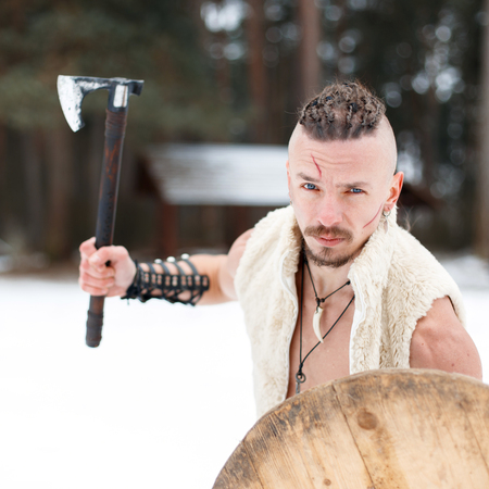 Warrior Viking with a scar with an ax and a wooden shield in the woods on a winter day Reklamní fotografie