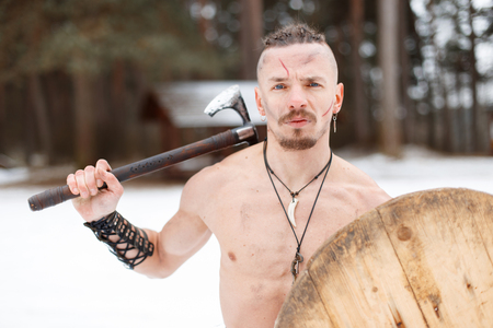 Ancient warrior with an ax and a wooden shield in the forest Reklamní fotografie