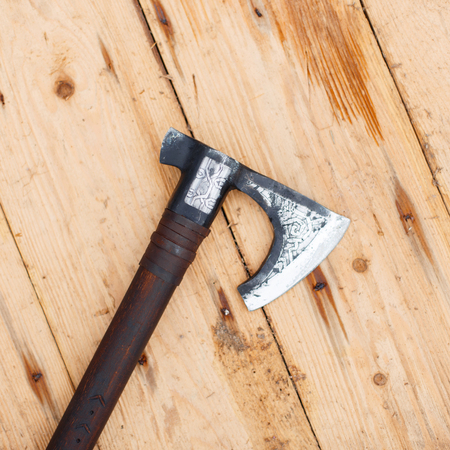Viking Ax lies on a wooden table, top view Stock Photo