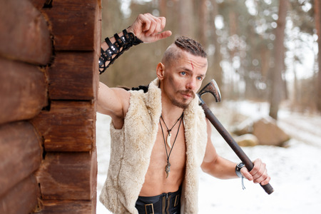 Viking warrior with an ax in a vest of wool near a wooden house