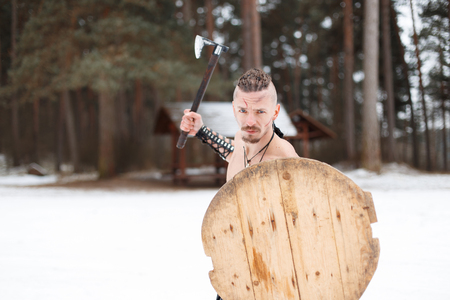 Viking warrior with an ax and shield in the nature on a winter day with snow