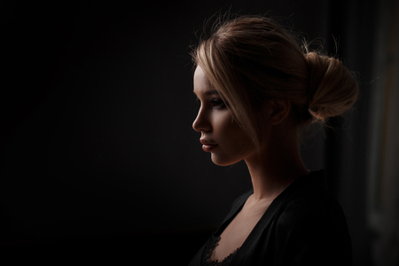 Portrait of a beautiful young woman in a fashion black dress on a black background. Female profile