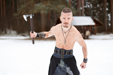 Warrior Viking Man with an Ax with a Naked Torso in the Winter Forest of Norway Reklamní fotografie
