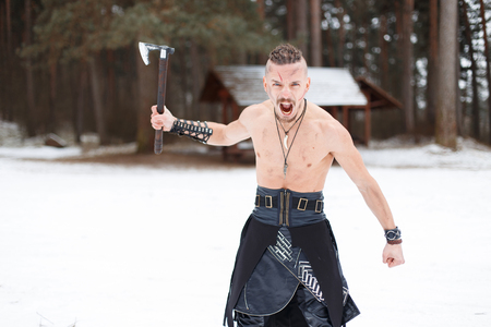 Warrior man viking with an ax screaming in the woods