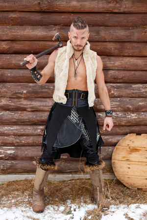 Warrior Viking with an ax in a waistcoat made of skin in boots near a wooden wall