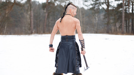 Viking warrior with an ax in the woods with snow