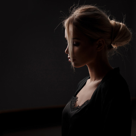 Young beautiful model woman with a hairstyle in a black fashion dress on a black background