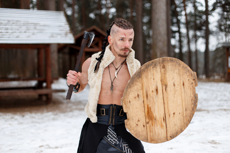 Ancient warrior viking with an ax and a wooden shield in the woods on a winter day Reklamní fotografie