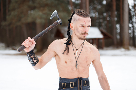 Viking man with an ax in the winter forest Reklamní fotografie