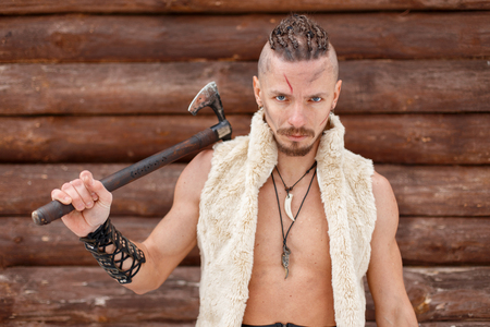 Viking man warrior with an ax in the skin of an animal near a wooden wall Reklamní fotografie