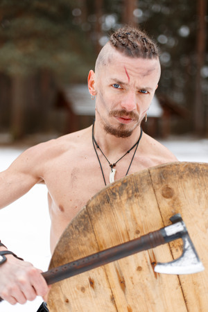 Warrior Viking with a scar with an ax and a shield in the woods