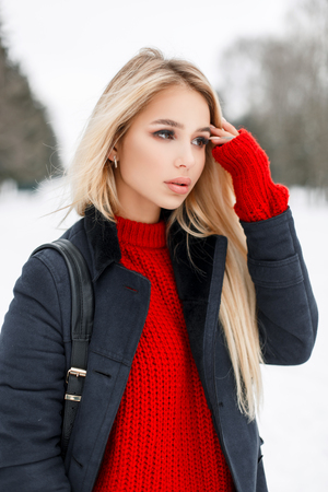Pretty young model girl in fashion coat with a red sweater with a stylish bag walks in the park
