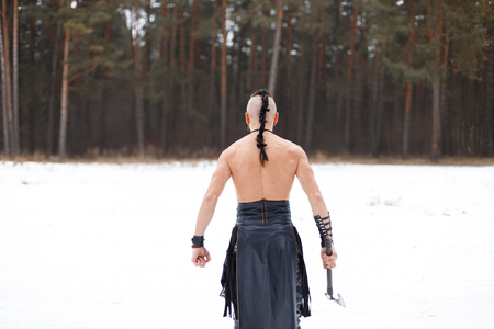 Viking warrior with an ax in front of the forest. The warrior stands with his back to the camera. Naked back. Reklamní fotografie