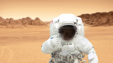 Astronaut on Mars shows a thumbs-up. Landscape of the red planet Mars.