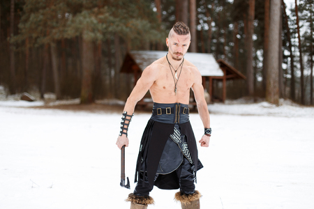 Warrior Viking with an Ax with a Naked Torso in the Winter Forest Reklamní fotografie