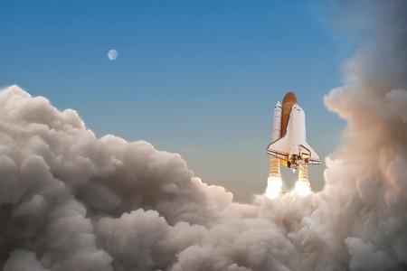 Wahadłowiec rozpoczyna swoją misję i wzbija się w niebo. Rakieta z chmurami dymu lecącymi w kosmos