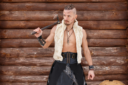 Warrior Viking with an Ax in a Vest of a Skin near a Wooden Wall