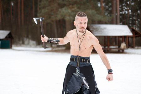 Male Viking with an ax in a leather skirt with a bare torso in the forest of Norway Reklamní fotografie