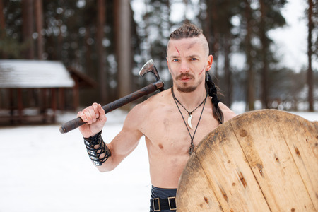 Ancient warrior man with an ax and shield in the forest Reklamní fotografie
