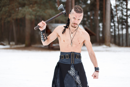 Viking warrior with an ax in the woods on a winter day