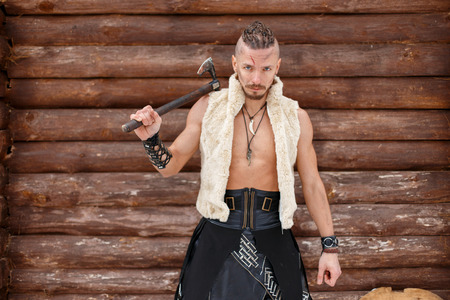 Viking warrior with an ax in a vest of a skin near a wooden wall