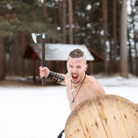 Viking warrior with a scar with an ax and shield attacks in the forest