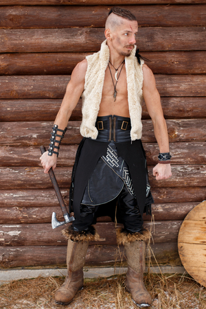 Viking man with an ax in a vest of skin in boots near a wooden wall Reklamní fotografie
