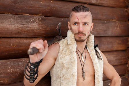 Viking with a scar with a hairstyle hold an ax in a vest of skin stands near a wooden wall