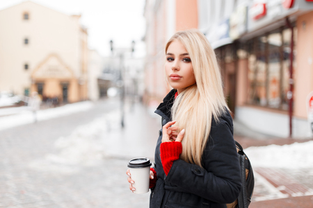 Stylish fashion model woman with coffee in a fashion winter coat with a bag walking in the city