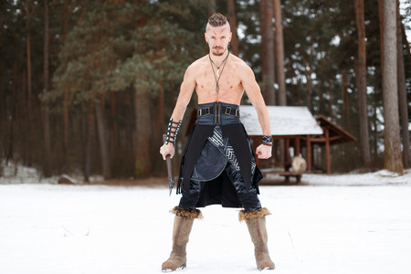 Viking man warrior with an ax in a leather skirt with boots with in the winter forest
