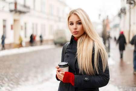 Beautiful young blonde woman with coffee in a fashion winter coat in the city Stock Photo