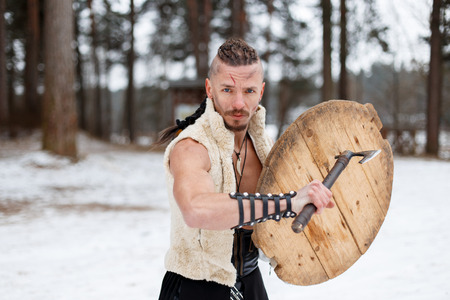 Ancient warrior with an ax and a wooden shield in a woolen vest in the forest