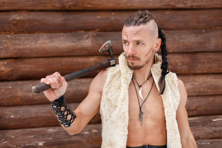 Male Viking with an ax in a warm waistcoat of skin near a wooden wall