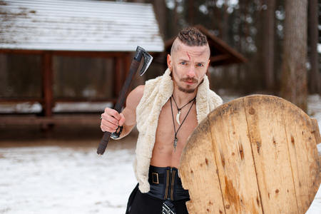 Ancient warrior a man with a scar with an ax and a shield in the woods on a winter day Reklamní fotografie - 106252472
