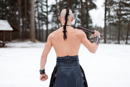 Viking with an ax stands in the woods with his back to the camera Reklamní fotografie