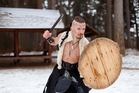 Ancient Warrior man viking with an ax and shield in the woods Reklamní fotografie