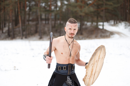 Viking with an ax and a shield in the forest with snow