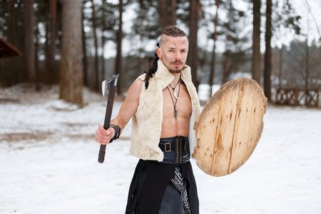 Viking with an ax and shield in woolen clothes in the forest