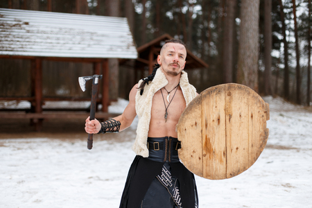 Viking warrior with an ax and shield in ancient clothes in the forest