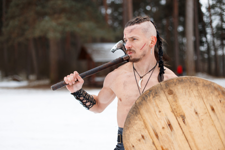 Ancient warrior with a pigtail with an ax and a shield in the forest on a winter day