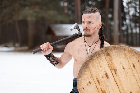 Viking man with a scar with an ax and a shield in the woods on a winter day