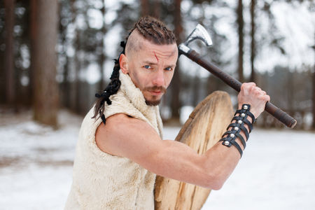 Viking warrior with an ax and a wooden shield in the forest on a winter day
