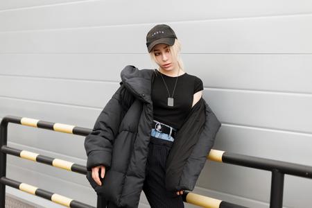 Modieuze schoonheidsvrouw in een zwarte wintermode jas en een zwarte pet met stijlvolle jeansbroek op straat