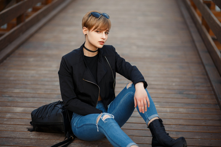 Fashionable beautiful young woman in a stylish black jacket with jeans and boots sitting on the wooden floor Stock Photo