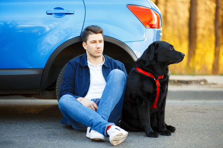 Handsome man in fashionable clothes with a dog sitting near the car. Enjoys traveling