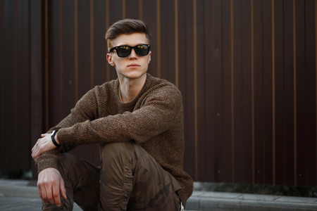 8a30ec4bf68 Handsome young hipster man in sunglasses in fashion clothes sitting on a  street near a metal