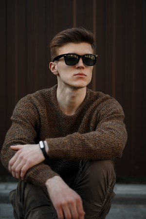 e45a0e3ade8 Handsome young American model man in sunglasses with a hairstyle in a  fashionable pullover sits near