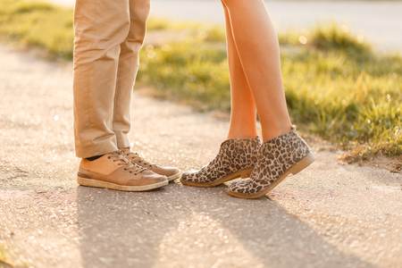 Young couple is kissing at sunset. Legs with stylish shoes close-up Stock Photo