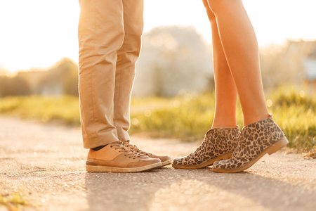 Young love couple kissing at sunset. Legs with shoes close-up